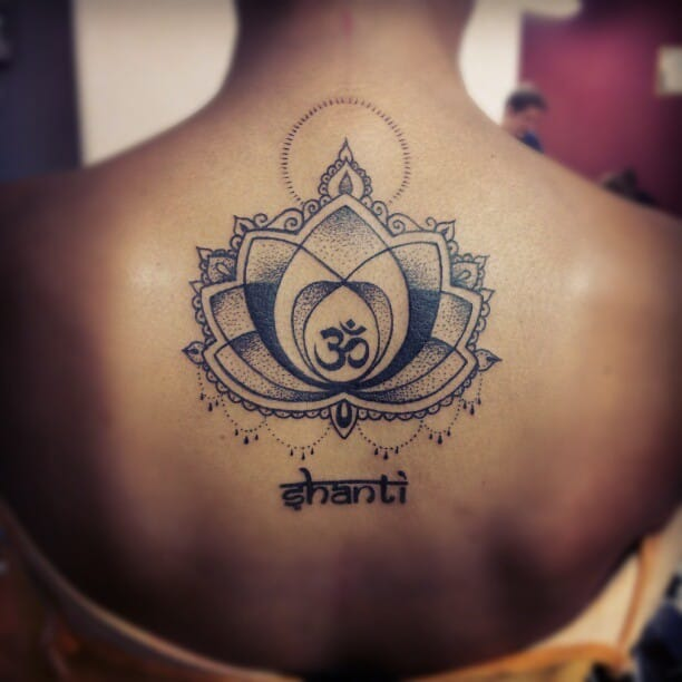 Black Ink Dotted Om Sign In Lotus Flower Tattoo On Girl Back Body