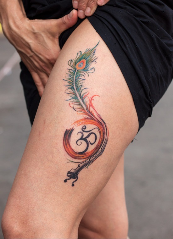 Lovely Peacock Feather Flute And Om Sign Tattoo On Girl Thigh