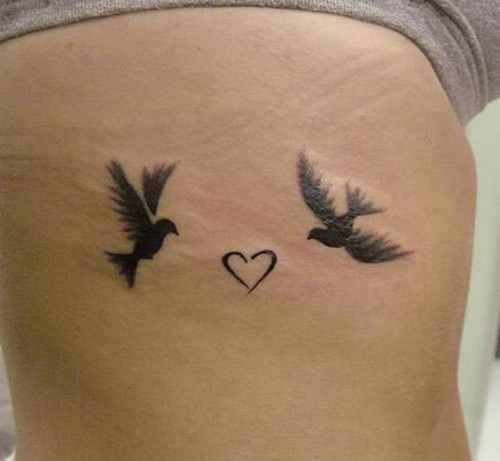 Cute Black Flying Bird With Heart Tattoo On Ribs Side