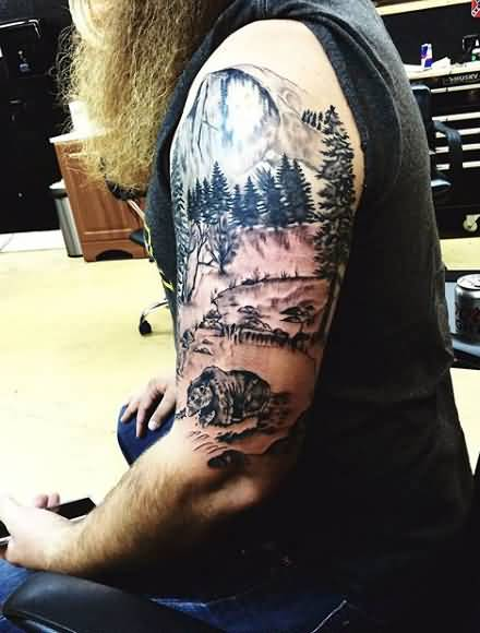 Nice Grey Forest And Bear Tattoo Made On Men Upper Arm