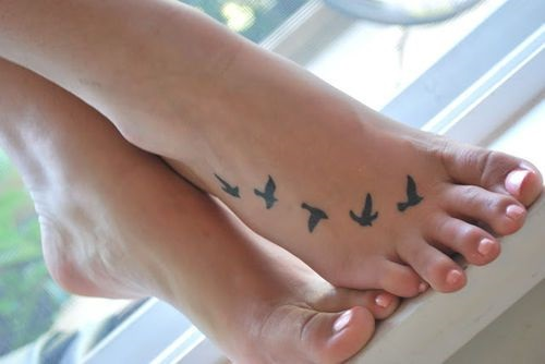 Nice Small Black Flying Bird Tattoo On Girl Foot