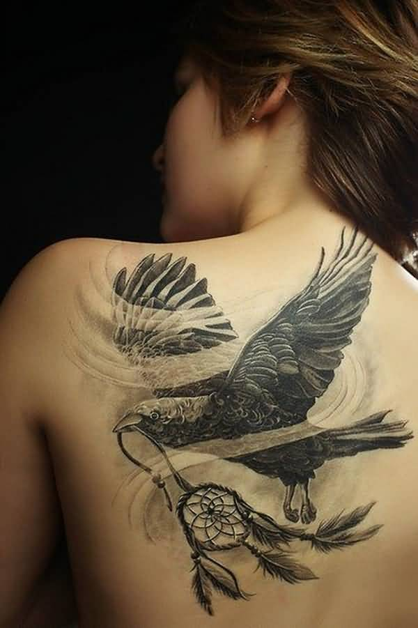 Outstanding Flying Crow Bird With Dreamcatcher Tattoo On Back Body