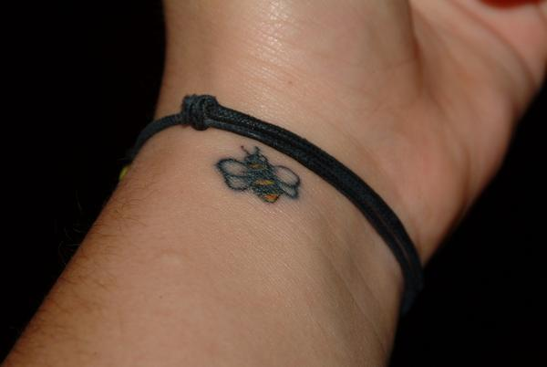 Outstanding Small Black Bee Tattoo Made On Girl Wrist