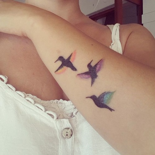 Wonderful Black Bird With Colorful Wings Tattoo On Arm
