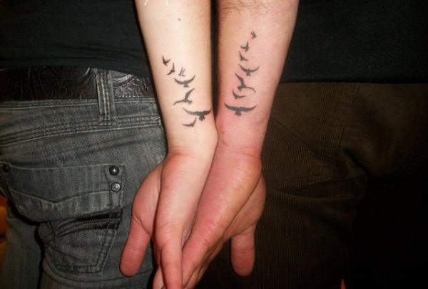 Wonderful Black Ink Flying Bird Tattoo For Couple Arm